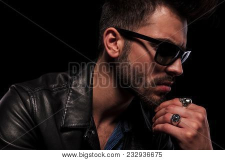 close up of thoughtful fashion man with leather jacket and sunglasses looking down to side, on black background
