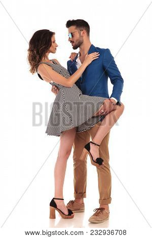 sensual young couple looking at each other with man holding her thigh while she leans on him, on white background