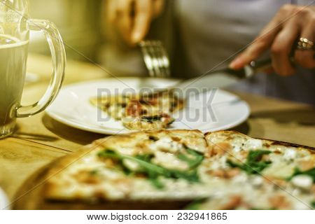 Concept: Eating Out. Blurred Background Image. Girl Is Eating A Pizza With A Knife And Fork. Pizza A