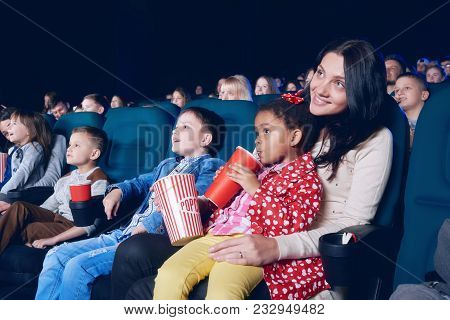 Sideview Of Mother And Daughter Watching Movie In The Cinema.
