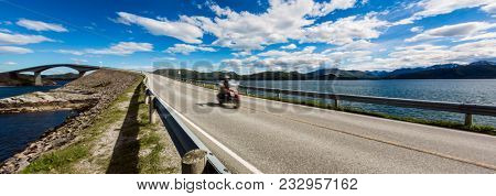 Biker rides a road with Atlantic Road in Norway. Atlantic Ocean Road or the Atlantic Road (Atlanterhavsveien) been awarded the title as