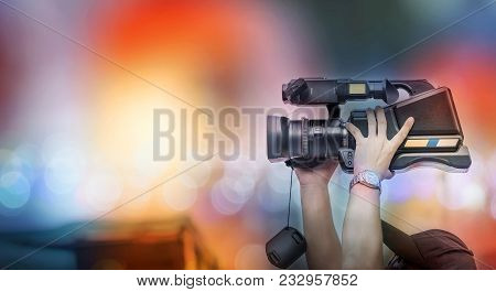 Video Camera Operator Working With His Equipment. Cameraman Lifts The Camcorder Above His Head While