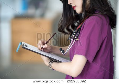 Nurse In Purple Uniform  Standing At Patient Room And Writing On Medical Chart