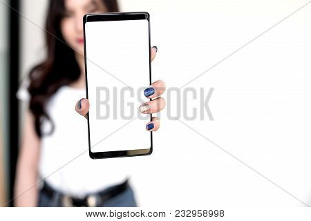 Young Woman Showing A White Screen Smartphone . Focus On Smartphone