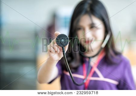 Beautiful Young Nurse Holding Stethoscope And  Listening To Green Pulse And Heart Rates