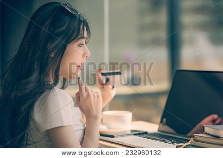 Young Pretty Woman Holding Credit Card And Using Laptop Computer. Online Shopping Concept