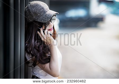 Beautiful Young Woman Wearing Hat And Sunglass Is Using Smartphone In The City