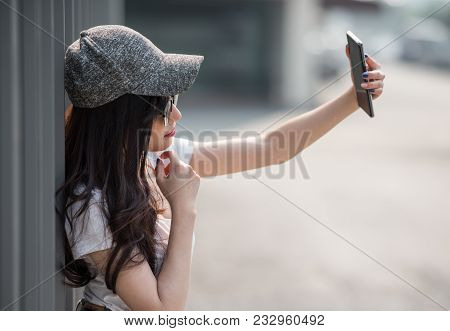 Young Beautiful Asian Woman Wearing Sunglasses Take Selfie With Smartphone With Sunlight Of Morning