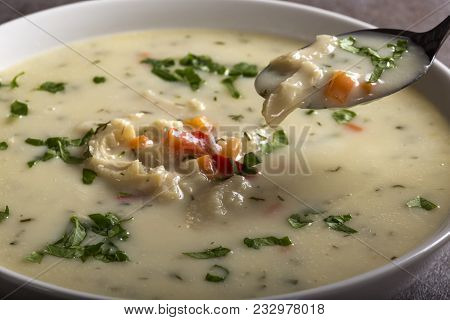 Close Up Of Spoon With Romanian Traditional Soup - Ciorba De Burta In White Bowl