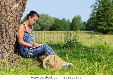 Young Indian Woman Sitting Against Tree Trunk Writing In Pasture