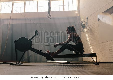 Fit Young Woman Working Out On A Rowing Machine At The Gym. Female Doing Cardio Exercise In Fitness