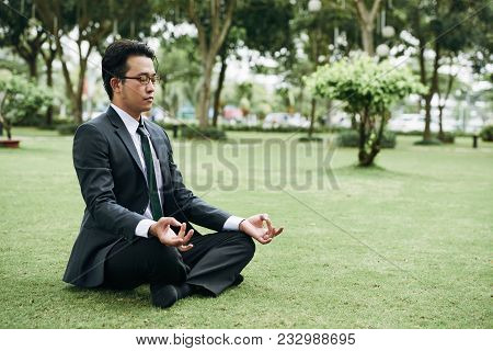 Young Asian Businessman In Suit Practicing Outdoor Meditation In Park