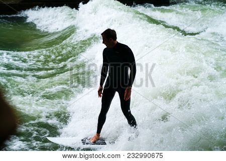 Munich Germany _ September 11 2017; Silhouette Of River Surfer Challenges Raging Green And Wiate Rap