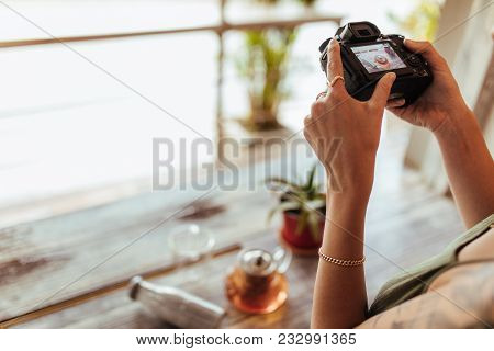 Close Up Of A Blogger Taking Photos Of A Glass Teapot, Bottle And A Plant Using A Professional Camer