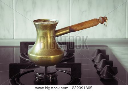 Cooking Coffee On A Gas Stove. Old Turkish Copper Pot For Brewing Coffee On Stove In The Kitchen. Ea