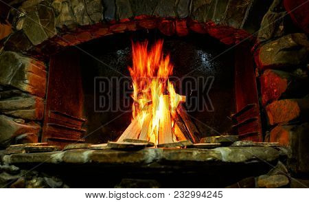 Burning Of A Tree In A Brick Fireplace. Fireplace With Flaming Fire.