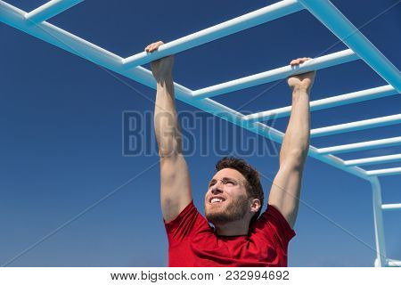 Fitness monkey bars man training arms muscles on jungle gym outdoors in summer. Athlete working out gripping climbing on ladder equipment at sport athletics centre. poster