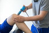 electronic therapy on knee used to treat pain. selective focus poster