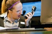 A woman-reception swears with the client of the hotel by phone. A woman is shouting into the phone's phone. Funny facial expressions, emotions, reaction of perception, stress, gilding, nerves. poster