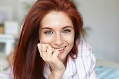 Close up portrait of attractive red haired young Caucasian woman with green eyes and perfect freckled skin spending morning in bed, wearing pajamas. Beauty, youth, leisure, people and lifestyle poster