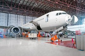 Passenger Airplane On Maintenance Of Engine And Fuselage Repair In Airport Hangar. Aircraft With Ope