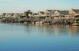 Sunset In Avalon. A Row Of Waterfront Luxury Summer Homes On The Back Bay In Avalon, New Jersey Duri