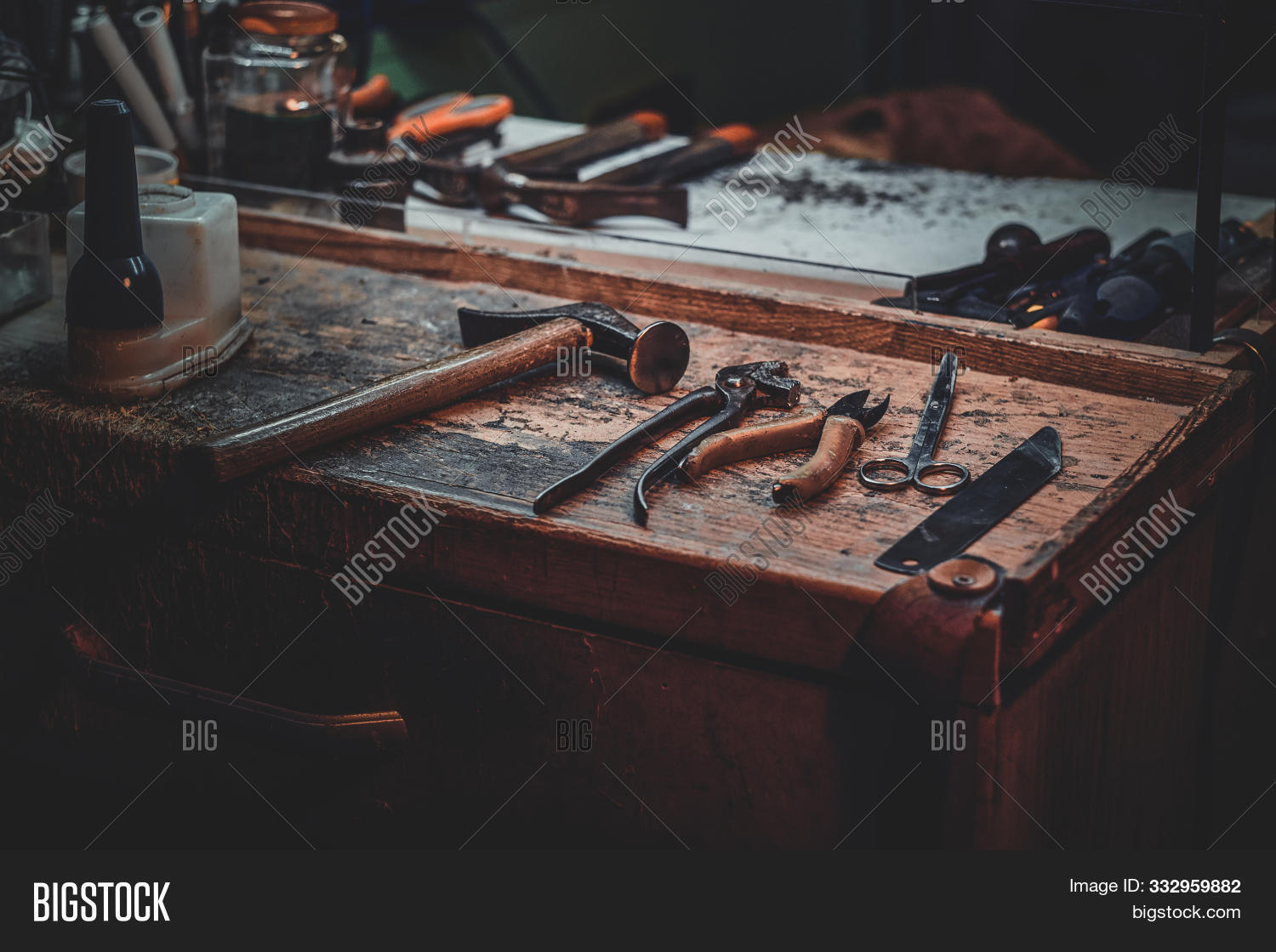 Workplace Of Cobbler With Necessary Tools On It At Dark Workshop.