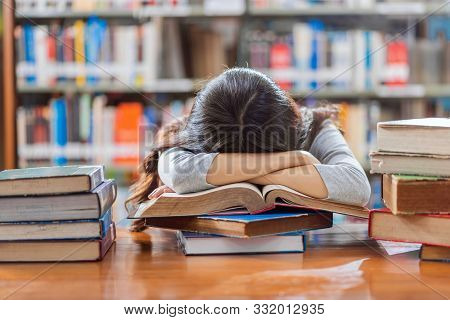 Asian Young Student In Casual Suit Reading And Sleeping On The Wooden Table With Various Book In Lib