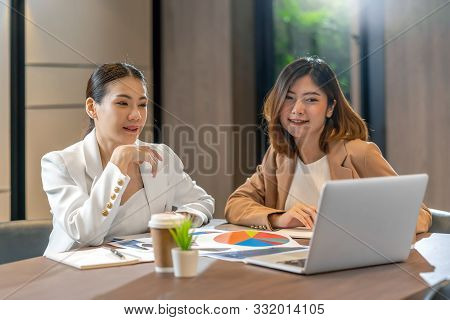 Two asian businesswomen working with the partner business via technology laptop in modern meeting room, office or working space, coffee break, partner and colleague concept poster