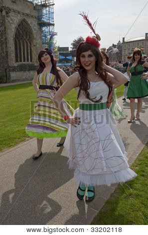 Performers in frilly dresses on Exeter Cathedral Green
