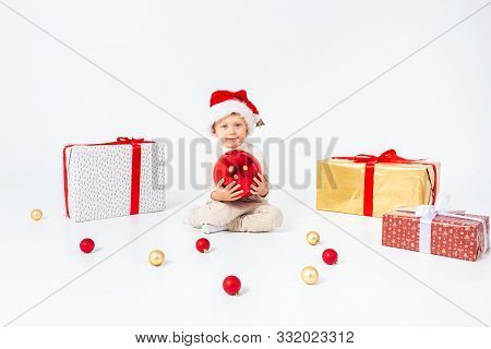 Little Boy Sitting Between Gifts And Holding Big Red Christmas Ball In Hands. Isolated On White Back