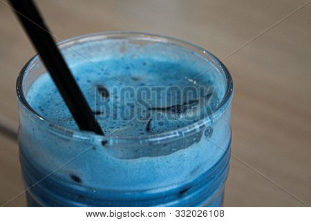 Glass Of Iced Pea Latte Blue Tea Cocktail With Milk On Wooden Table With Black Straw And Ice. Copy S