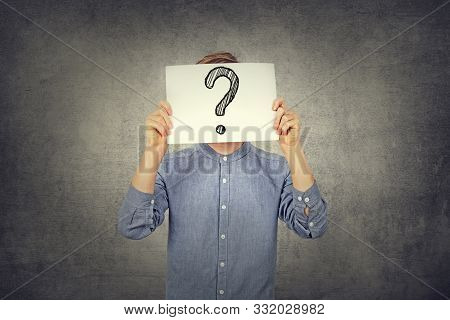 Tennager Boy Using A White Paper With Drawn Question Mark On Gray Wall Background. Question Mark, Sy