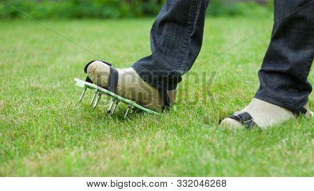Woman Wearing Spiked Lawn Revitalizing Aerating Shoes, Gardening Concept.