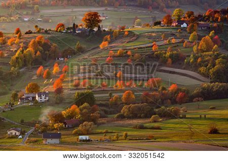 Fall In Slovakia. Meadows And Fields Landscape Near Hrinova. Autumn Colored Cherry Trees At Sunset