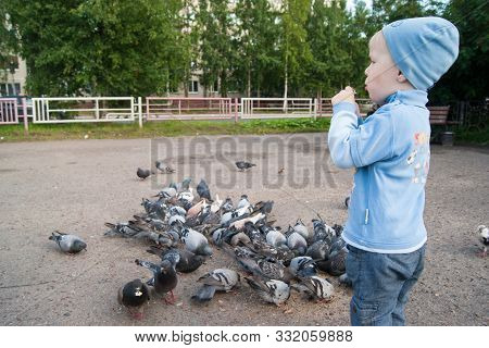 Three-year-old White Boy In A Blue Hat, Jeans And Sandals On A Cool Summer Day Enthusiastically Feed