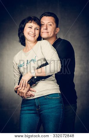 Playful Mature Married Couple Photographed In The Studio. Handsome Man In Jeans And Smiling Woman In