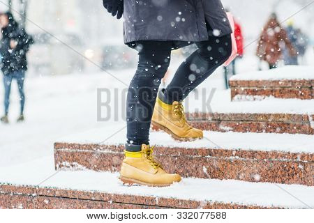 A Young Woman In Yellow Leather Boots Rises On Icy Snowy Granite Steps In Urban Environment. Winter