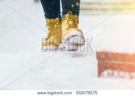 A Woman In Yellow Leather Shoes Is Walking Along A Snowy Pavement. Winter Walk. Abstract Winter Weat