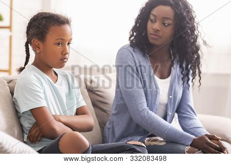 Disobedient Child. Disappointed Black Mother Looking At Her Little Daughter With Reproach, Sitting O