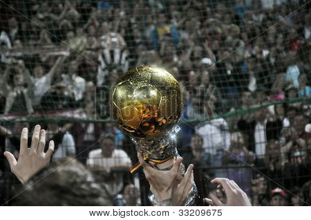 Golden ball trophy and soccer supporters