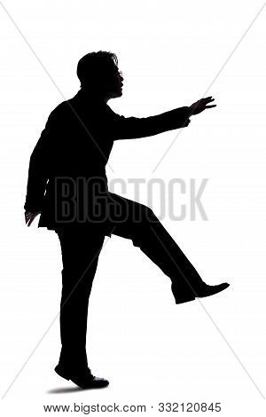 Silhouette Of A Backlit Model Posing As A Businessman On A White Background.  He Is Jumping Up Or Le