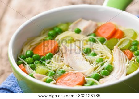 Fresh Homemade Chicken Noodle Soup With Carrot, Peas And Celery In Green Soup Bowl (selective Focus,