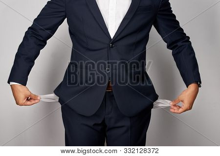 Young Businessman Showing Empty Pockets, Studio Shot, Isolated On White Background
