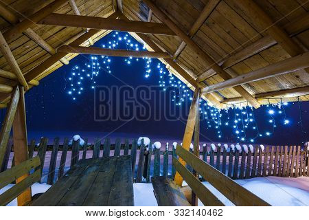 Wooden Arbor With Christmas Lights Stands On A Ski Slope In The Evening Foggy Winter Time Against A
