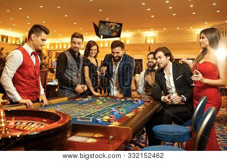 Group Happy People Make Bets Gambiling At The Roulette Table In The Casino.