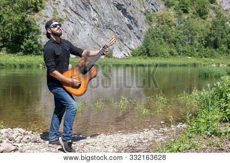 Young Hipster Bearded Guy, Man In A Cap Plays The Guitar With Lowered Strings Against The Backdrop O