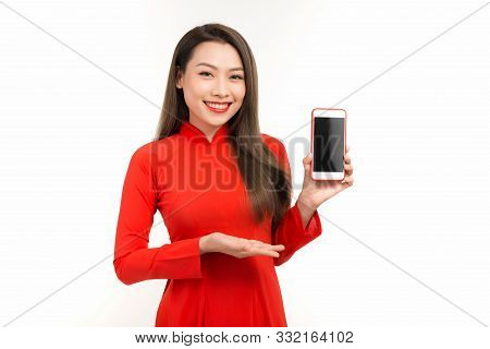 Attractive Woman In Ao Dai Dress Showing Screen Mobile Phone, Isolated On White Background