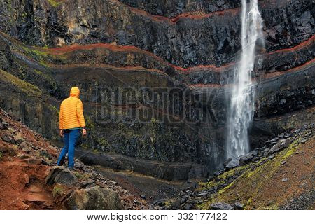 Tourist in front of Hengifoss canyon and waterfall, the third highest waterfall in Iceland, surrounded by basaltic strata with red layers of clay between the basaltic layers.