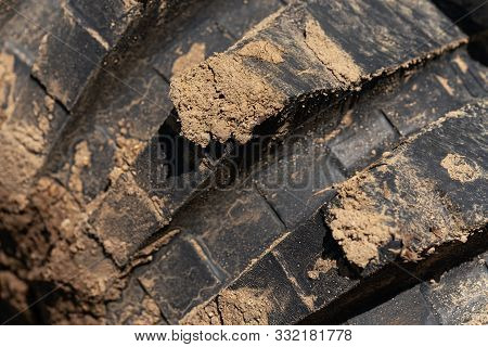 Close-up View Of Old Used Rubber Mud Terrain Tire With Worn Wear-resistant Tread. Black Muddy Off-ro